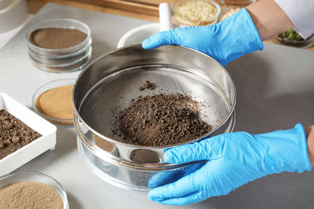Wetenschapper verpulveren en zeven bodemmonsters aan tafel, close-up. Laboratorium analyse