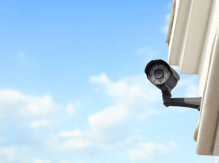 Modern CCTV security camera on building outdoors. Space for text Stock Photo
