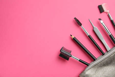 Set of professional eyebrow tools on pink background, flat lay. Space for text Фото со стока