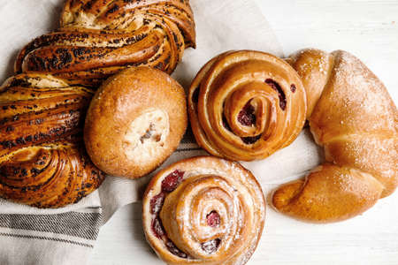 Different delicious fresh pastries on white wooden background, flat lay 版權商用圖片