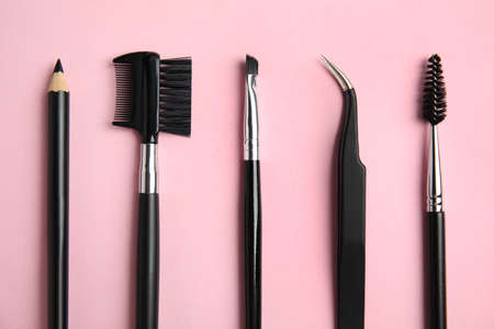Set of professional eyebrow tools on pink background, flat lay