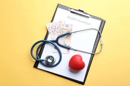 Flat lay composition with medical insurance form, money, heart and stethoscope on yellow background