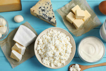 Different dairy products on blue wooden table, flat lay