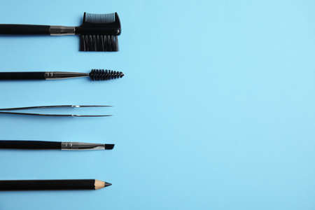 Set of professional eyebrow tools on blue background, flat lay. Space for text