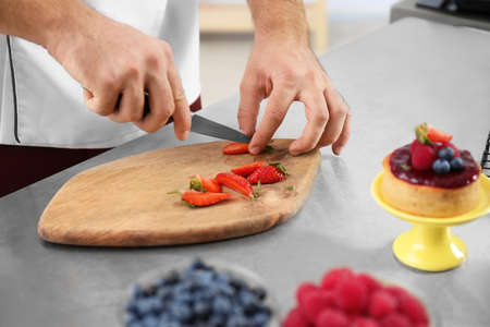 Male pastry chef cutting berries at table in kitchen, closeup