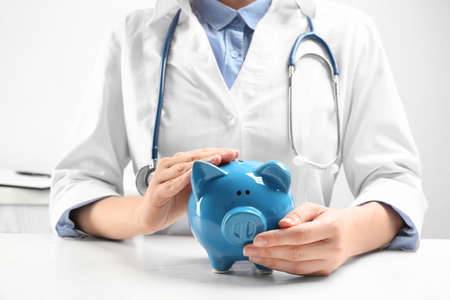 Doctor with piggybank at white table indoors, closeup. Medical insurance concept Stok Fotoğraf