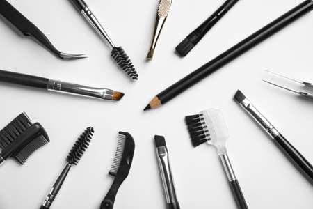 Set of professional eyebrow tools on white background, flat lay