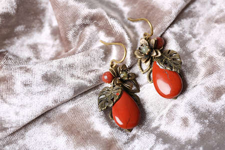 Beautiful pair of metal earrings with red jasper gemstones on light fabric, above view Stock Photo