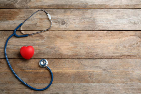 Stethoscope and red heart on wooden background, flat lay with space for text. Health insurance concept