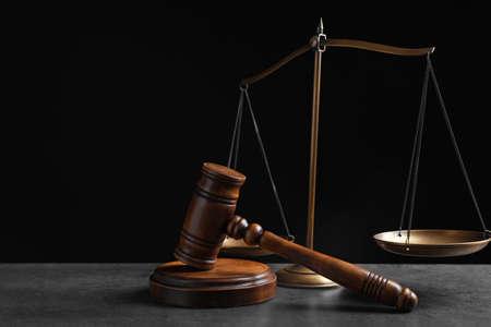 Rechter's hamer en schalen op grijze tafel tegen zwarte achtergrond. strafrechtelijk concept Stockfoto