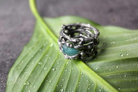 Beautiful silver ring with apatite gemstone on green leaf, closeup
