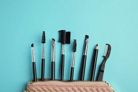 Set of professional eyebrow tools on turquoise background, flat lay