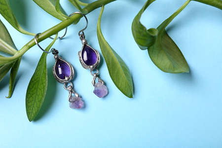 Beautiful pair of silver earrings with amethyst gemstones and leaves on light blue background, above view