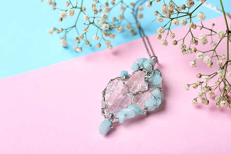 Beautiful silver pendent with pure quartz gemstones and flowers on color background