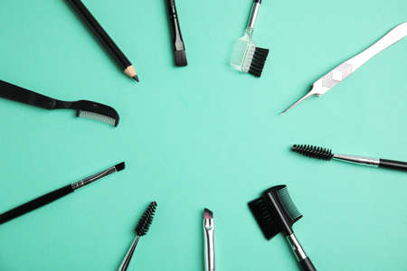 Set of professional eyebrow tools on turquoise background, flat lay. Space for text