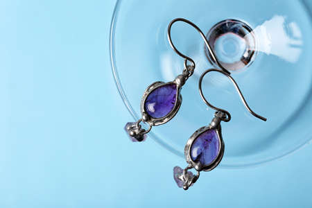 Beautiful pair of silver earrings with amethyst gemstones on blue background, above view Stock Photo