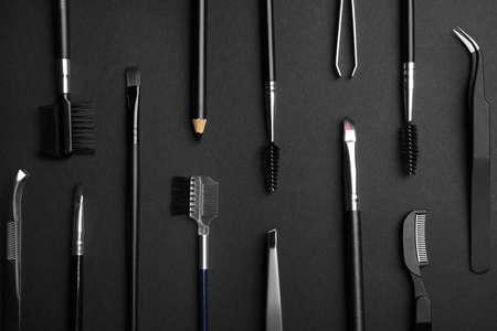 Set of professional eyebrow tools on black background, flat lay