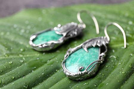 Beautiful pair of silver earrings with amazonite gemstones on green leaf, closeup