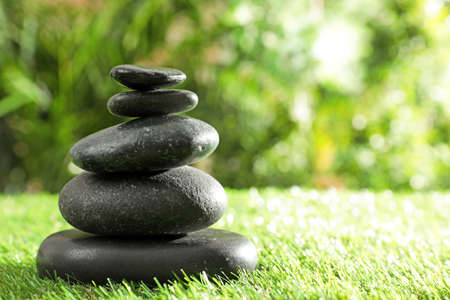 Stack of stones on green grass against blurred background, space for text. Zen concept
