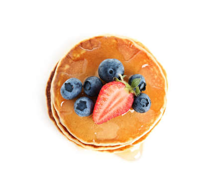 Stack of delicious pancakes with fresh berries and syrup on white background, top view Standard-Bild