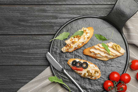 Slate plate of delicious chicken bruschettas on dark wooden table, flat lay. Space for text