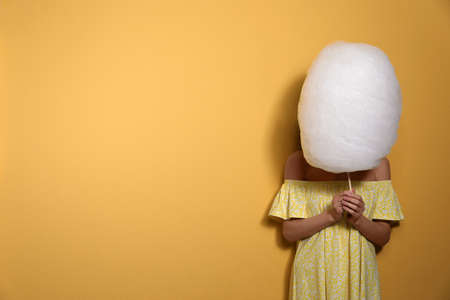 Young woman hiding behind tasty cotton candy on yellow background. Space for text Reklamní fotografie