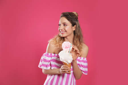 Portrait of young woman holding cotton candy dessert on pink background