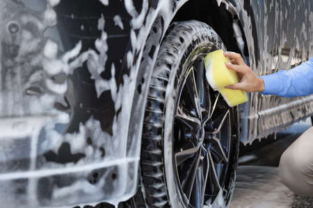 Businessman cleaning auto with sponge at self-service car wash, closeup Stok Fotoğraf