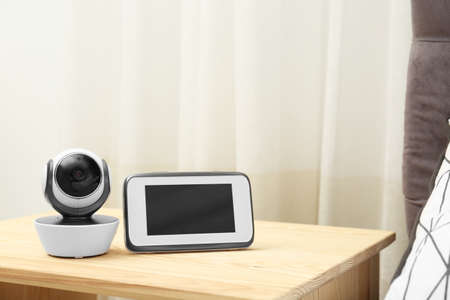 Baby monitor with camera on table in room, space for text. Video nanny Stock Photo