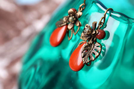 Beautiful pair of metal earrings with red jasper gemstones on glass stand, closeup