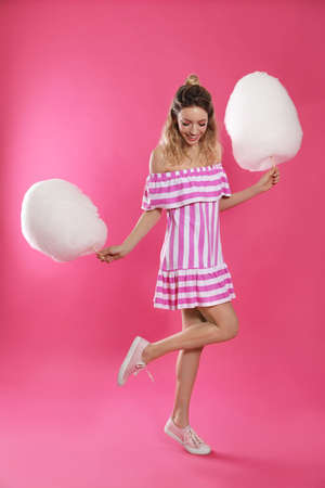 Full length portrait of pretty young woman with cotton candy on pink background