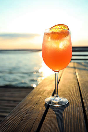 Glass of fresh summer cocktail on wooden table outdoors at sunset Stock Photo
