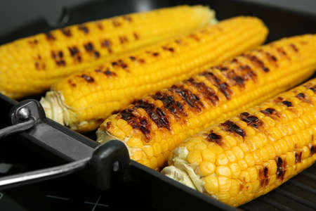 Grill pan with tasty fresh corn cobs on stove, closeup