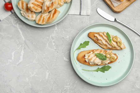 Plate of delicious chicken bruschettas on grey marble table, flat lay. Space for text