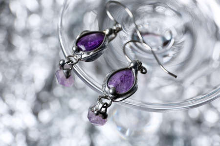 Closeup of beautiful pair of silver earrings with amethyst gemstones on blurred background