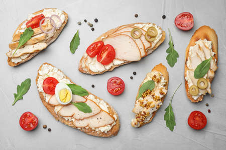 Different delicious chicken bruschettas on light grey table, flat lay