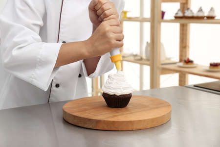 Young female pastry chef decorating cupcake with cream at table in kitchen, closeup