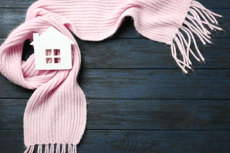House model and pink scarf on dark blue wooden background, top view with space for text. Heating efficiency