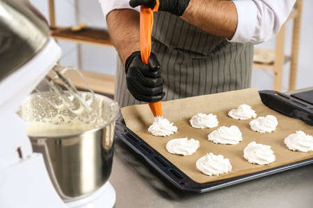 Pastry chef preparing meringues at table in kitchen, closeup