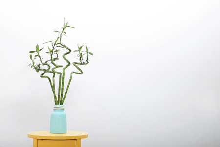 Vase with bamboo stems on yellow table against light wall, space for text