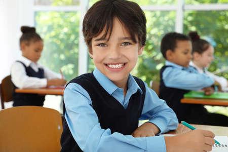 Boy wearing new school uniform in classroom Stock fotó