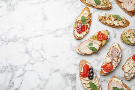 Different delicious chicken bruschettas on white marble table, flat lay. Space for text