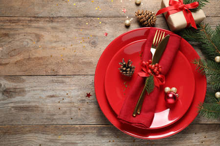 Beautiful Christmas table setting on wooden background, top view. Space for text