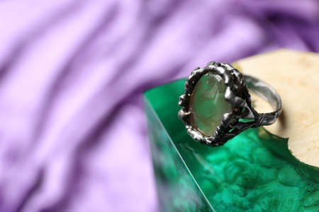 Beautiful silver ring with prehnite gemstone on textured surface. Space for text Stock Photo
