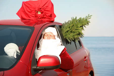 Authentic Santa Claus with fir tree and bag full of presents on roof driving modern car  near sea Stock Photo