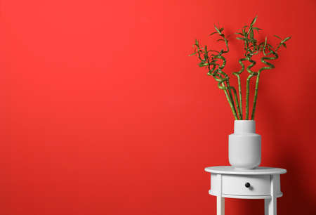 Vase with bamboo stems on white table against red background, space for text