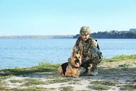 Man in military uniform with German shepherd dog near river, space for text