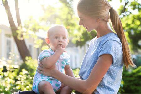 Niñera adolescente con lindo bebé al aire libre en un día soleado