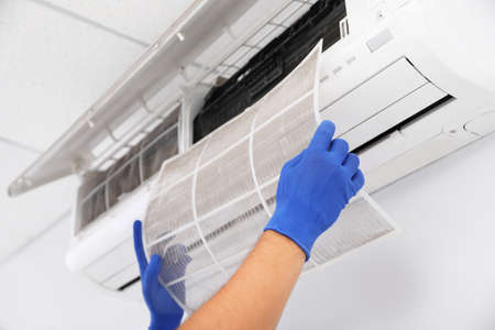 Professional technician maintaining modern air conditioner indoors, closeup