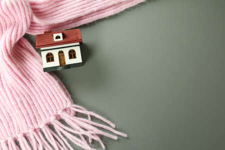 Wooden house model and pink scarf on  grey background, top view with space for text. Heating efficiency Reklamní fotografie